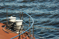 Metal bollard with mooring lines on deck of a ship. Royalty Free Stock Photography