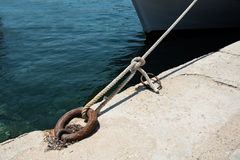 Metal bollard and rope securing a ship Stock Images