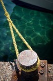 Metal bollard and rope securing a ship Stock Photo