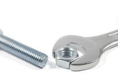 Metal Bolt And Chrome-Vanadium Spanner Gripping Nut Isolated On White Background. Studio Shot Stock Image