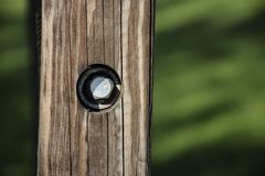 METAL BOLT IN A WOODEN FENCE. A sturdy metal bolt keeps a wooden post together in a park royalty free stock image