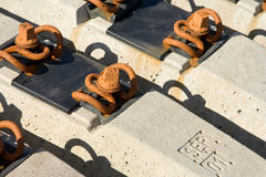 A metal bolts on a rail sleepers. A row of a concrete rail sleepers and rusty bolts Royalty Free Stock Photos