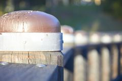 Metal bounded wooden pylons in a row stock photography