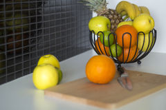 Metal bowl with fruis. A bowl with fruits standing on table in a modern kitchen Stock Photos
