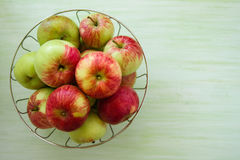 Metal bowl with green, yellow and red apples on the green wooden background. Stock Photos