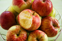 Metal bowl with green, yellow and red apples and one bitten apple closeup. Metal bowl with green, yellow and red apples and one bitten apple closeup, top view Royalty Free Stock Photos