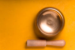 Metal bowl with wooden stick on the yellow table on the right Stock Image