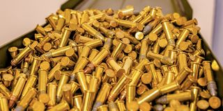 Metal box filled with cylindrical golden bullets stock photos