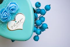 Metal box in the form of heart with the inscription `I Love You` and with roses. Blue color. St. Valentine`s Day. Berries inside. Metal box in the form of heart stock photo