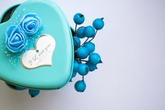 Metal box in the form of heart with the inscription `I Love You` and with roses. St. Valentine`s Day. Berries inside. Metal box in the form of heart with the royalty free stock image
