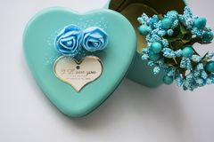 Metal box in the form of heart with the inscription `I Love You` and with roses. Blue color. Turquoise. St. Valentine`s Day. White background. Flowers inside stock images