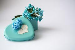 Metal box in the form of heart with the inscription `I Love You` and with roses. Blue color. Turquoise. St. Valentine`s Day. White background. Flowers inside royalty free stock images