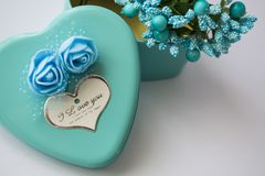 Metal box in the form of heart with the inscription `I Love You` and with roses. Blue color. Turquoise. St. Valentine`s Day. White background. Flowers inside royalty free stock image