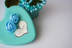 Metal box in the form of heart with the inscription `I Love You` and with roses. Blue color.St. Valentine`s Day. Flowers inside. Metal box in the form of heart stock photos