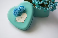 Metal box in the form of heart with the inscription `I Love You` and with roses. Blue color. Turquoise. St. Valentine`s Day. White background. Flowers inside stock photo