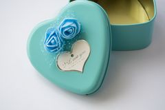 Metal box in the form of heart with the inscription `I Love You` and with roses. Blue color. St. Valentine`s Day. Metal box in the form of heart with the royalty free stock photos