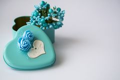 Metal box in the form of heart with the inscription `I Love You` and with roses. White background. Flowers inside. Metal box in the form of heart with the royalty free stock photo