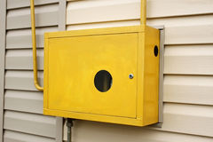 Metal box with a gas device inside. Yellow metal box with a gas device inside hanging outdoors on the wall of a residential building covered with siding stock images