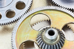 Metal brass mechanic gears and cogwheels on scratched background Royalty Free Stock Photography