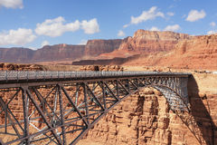 The metal bridge in abrupt coast of desert. The easy metal bridge through the river Colorado in abrupt coast of desert from red sandstone royalty free stock images