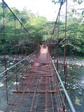 Across the Bridge. A metal bridge across a river to the forest royalty free stock photography