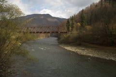 Metal bridge over the river. Among the mountains Stock Photos