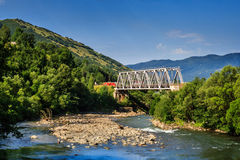 Metal bridge over the river in the mountains. White metal bridge over the river in the mountains on serene summer day Royalty Free Stock Photo