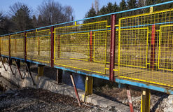 Metal bridge painted in vivid blue, yellow and red. Metal bridge of the U section and expanded metal and woven wire, painted in vivid blue, yellow and red Royalty Free Stock Photography
