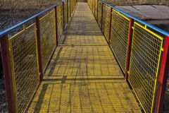 Metal bridge painted in vivid blue, yellow and red. Metal bridge of the U section, expanded metal and woven wire, painted in vivid blue, yellow and red, across Royalty Free Stock Photos