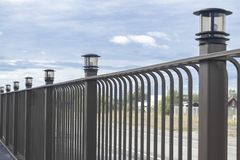 Free Metal Brown Fence. There Are Lamps On Poles. Day. Perspective. Royalty Free Stock Photo - 164576335