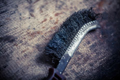 Metal brush on wooden plank Royalty Free Stock Photography