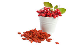 Metal bucket with barberries near heap of goji berries. On white background Royalty Free Stock Images