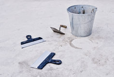 Metal bucket with cement and spatulas Royalty Free Stock Image