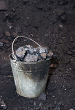 Metal bucket full of lumps of coal. On the black Royalty Free Stock Photography