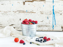 Metal bucket of strawberries, raspberries. Blueberries and mint leaves, white wooden background, front view Royalty Free Stock Photography
