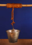 A metal bucket suspended above a wishing well - blue background Royalty Free Stock Image