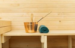 Metal bucket and towel in sauna. Royalty Free Stock Photography