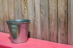 A metal bucket of water. Pink wooden bench. Rustic wood planks b stock photography