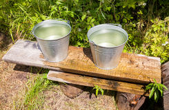Metal buckets with cold water standing on a bench Stock Photography