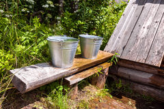 Metal buckets with cool water standing on a bench Stock Images