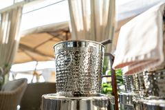 Metal buckets with an ice for cooling drinks. Service area the waiter in restaurant. silver shiny container. Catering. Set-up ready for the event to begin stock photos