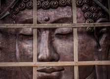 A metal buddha sculpture with wood on front of it. Java Royalty Free Stock Photos