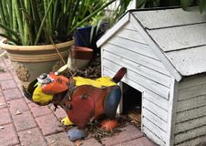 Metal bull dog statue defending house. A cute colorful bull dog statue made from metal is defending his white dog house showing its vicious and large teeth stock photos