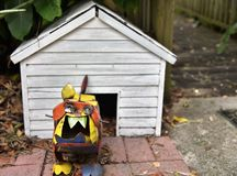Metal bull dog statue defending house. A cute colorful bull dog statue made from metal is defending his white dog house showing its vicious and large teeth royalty free stock photography