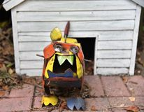 Metal bull dog statue defending house. A cute colorful bull dog statue made from metal is defending his white dog house showing its vicious and large teeth stock photography