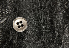 Metal button on black leather background Royalty Free Stock Photos