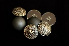 Metal buttons on black bacground. Photograph of grey metal buttons on a black background. All buttons have intricate design and patterns Royalty Free Stock Image