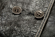 Metal buttons on black leather clothing Royalty Free Stock Photography