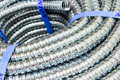 Metal cable protection conduit electric line. Stock Photos