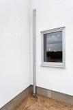 Metal a calha da chuva em uma parede branca com janela Fotografia de Stock